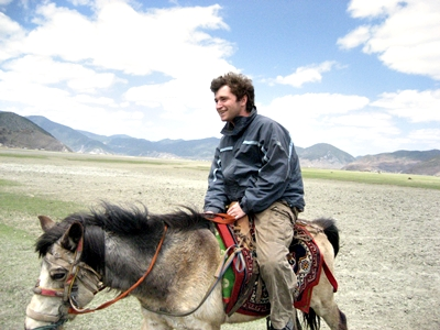 Suher riding a horse through a Tibetan meadow in the town of Shangri-La (Northern Yunnan, China).